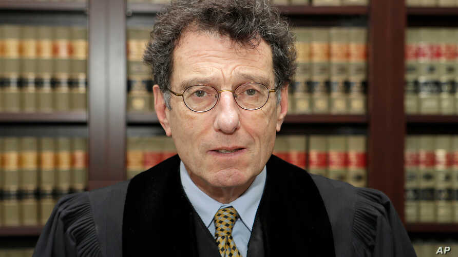 FILE - U.S. District Judge Dan Polster poses for a portrait in his office in Cleveland, Ohio, Jan. 11, 2018. He rejected efforts by drugmakers to dismiss claims they caused the nation's opioid crisis, clearing the way for a scheduled landmark trial.