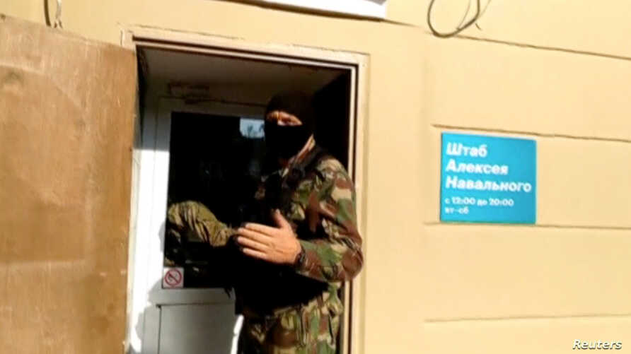 A still image taken from video shows a masked law enforcement officer addressing journalists during a raid in a local office of Kremlin critic Alexei Navalny, in Perm, Russia, Sept. 12, 2019.