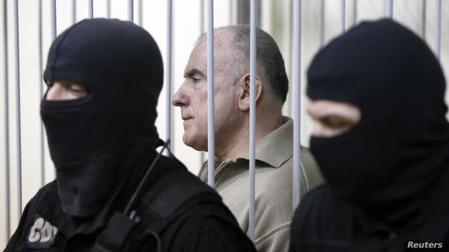 FILE - Oleksiy Pukach, former head of the surveillance department of Ukraine's Interior Ministry, looks out from a defendant's cage during his trial in the murder of journalist Heorhiy Gongadze, in Kyiv, Ukraine, 29, 2013.