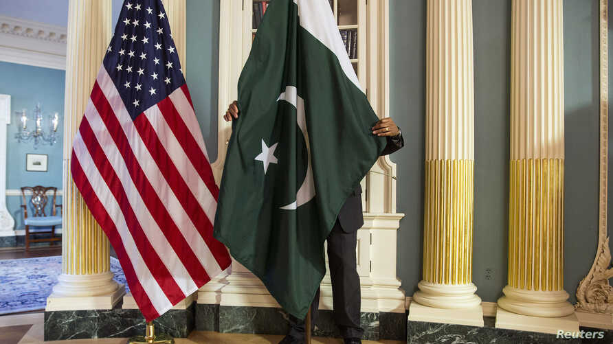 A State Department employee adjusts a Pakistani national flag before a meeting of U.S. and Pakistani officials at the State Department in Washington, Feb. 19, 2015. A U.S. Defense Department delegation is traveling to Pakistan for talks next week.
