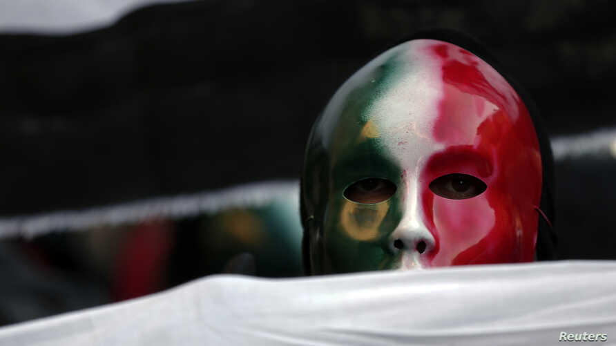 "FILE - A member of the Casapound far-right organization wears a mask in the colors of the Italian flag before a demonstration organized by ""People from pitchfork movement"" to protest against economic insecurity and the government in Rome, Dec. 18, 2013."
