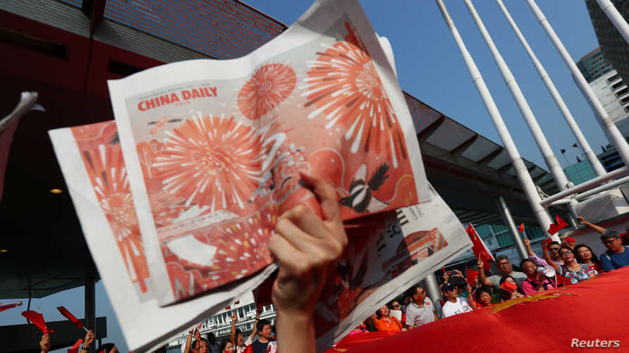 A Pro-China supporter holds up copies of the China Daily while others wave China's national flags at Harbour City, during China's National Day in Hong Kong, China, Oct. 1, 2019.