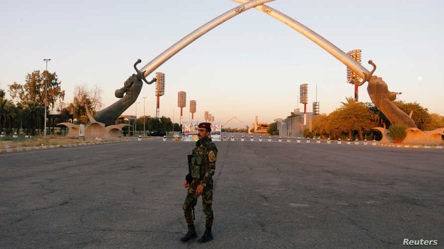 """FILE - An Iraqi security officer walks near the """"Arch of Victory"""" memorial in the Green Zone of Baghdad, Iraq July 15, 2019."""