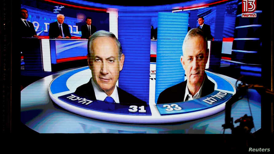 The results of the exit polls are shown on a screen at Benny Gantz's Blue and White party headquarters, following Israel's parliamentary election, in Tel Aviv, Israel, Sept. 17, 2019.