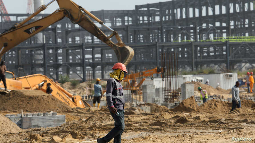 A worker walks past excavators at a construction site of the Dangote refinery in Ibeju Lekki district, on the outskirts of Lagos, Nigeria, August 7, 2019.