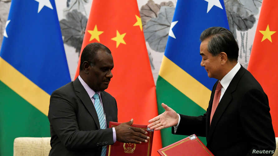 Chinese State Councilor and Foreign Minister Wang Yi reaches out to shake hands with Solomon Islands Foreign Minister Jeremiah Manele during a ceremony to mark the establishment of diplomatic ties between the two nations.