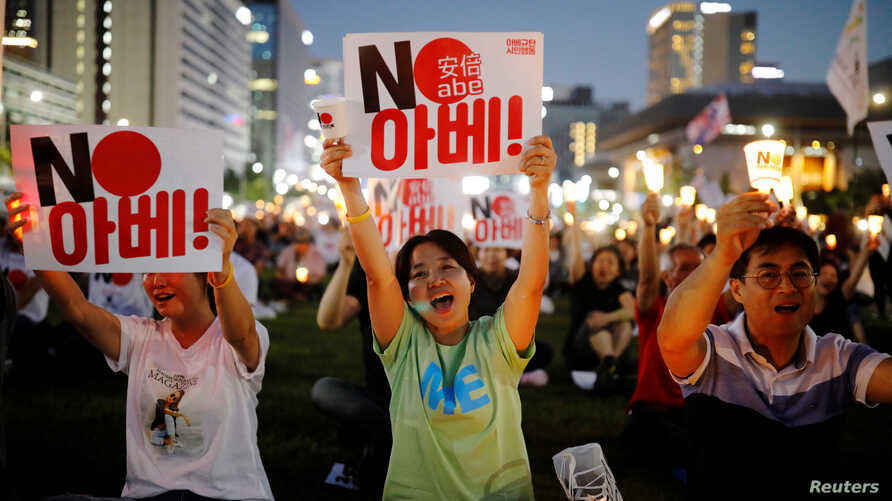 FILE -  South Korean people chant slogans during an anti-Japan rally in Seoul, South Korea, Aug. 24, 2019.