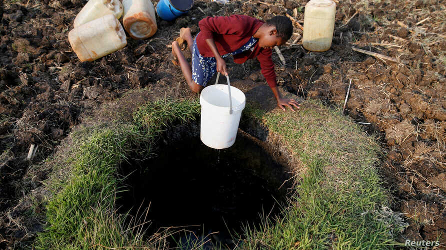 A woman fetches water from a well in Warren Park suburb, Harare, Zimbabwe.