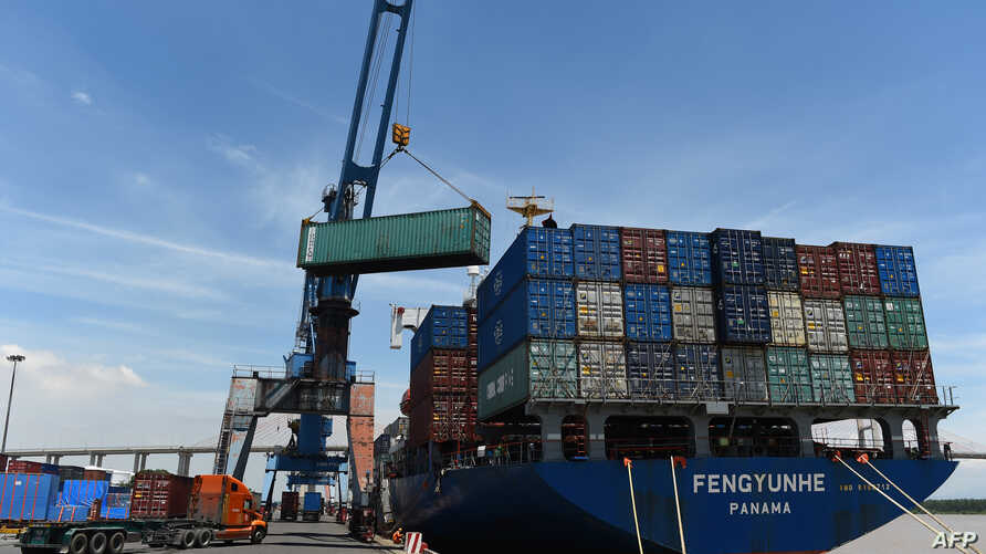 Containers are transferred from a truck to cargo ship at the international cargo terminal of a port in Hai Phong city on August…