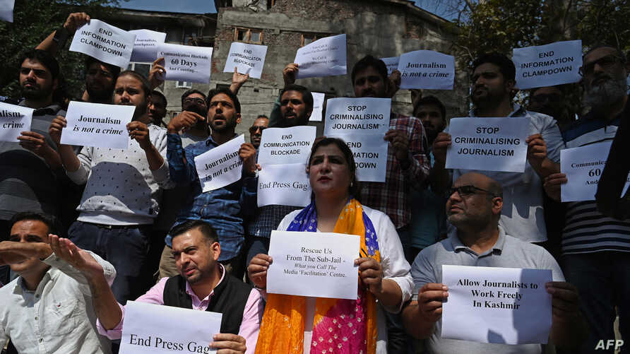 Journalists hold signs during a protest against the ongoing restrictions of the internet and mobile phone networks at the Kashmir Press Club during a lockdown in Srinagar, Oct. 3, 2019.