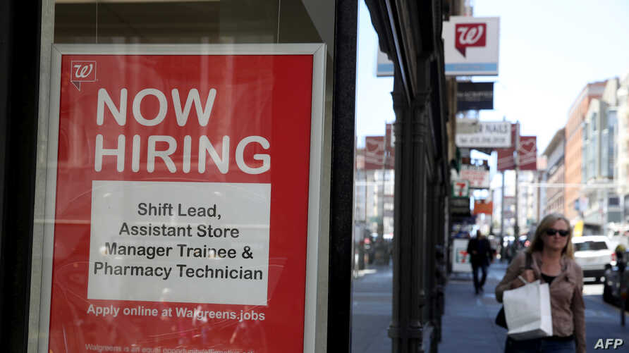 (FILES) In this file photo taken on June 06, 2019 a now hiring sign is posted in the window of a Walgreens store in San…