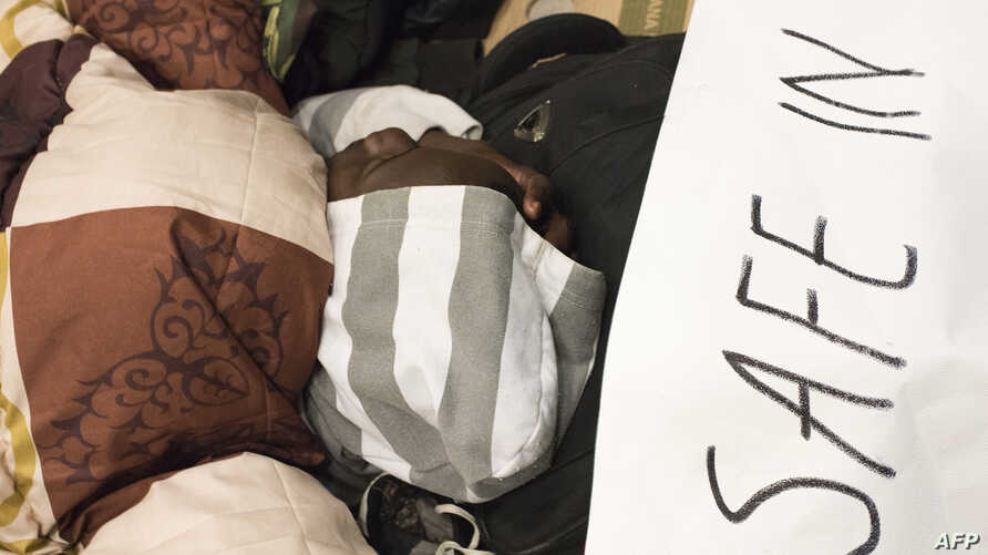 "A man sleeps close to a banner reading ""We are not safe in South Africa, plz help us to leave this country"" where dozens of…"