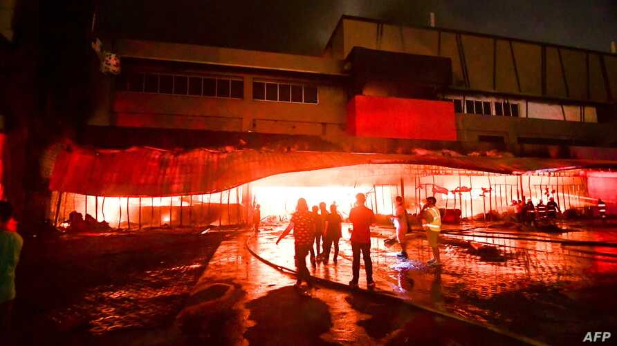 Firemen try to put out a fire inside a mall following a 6.4-magnitude quake in General Santos City, in southern island of Mindanao, on October 16, 2019.