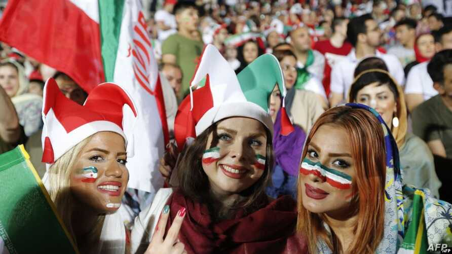 FILE -- Iranian women cheer as they wave their country's flag after authorities in a rare move allowed a select female group into Tehran's Azadi Stadium to watch a friendly soccer match between Iran and Bolivia, Oct. 16, 2018.