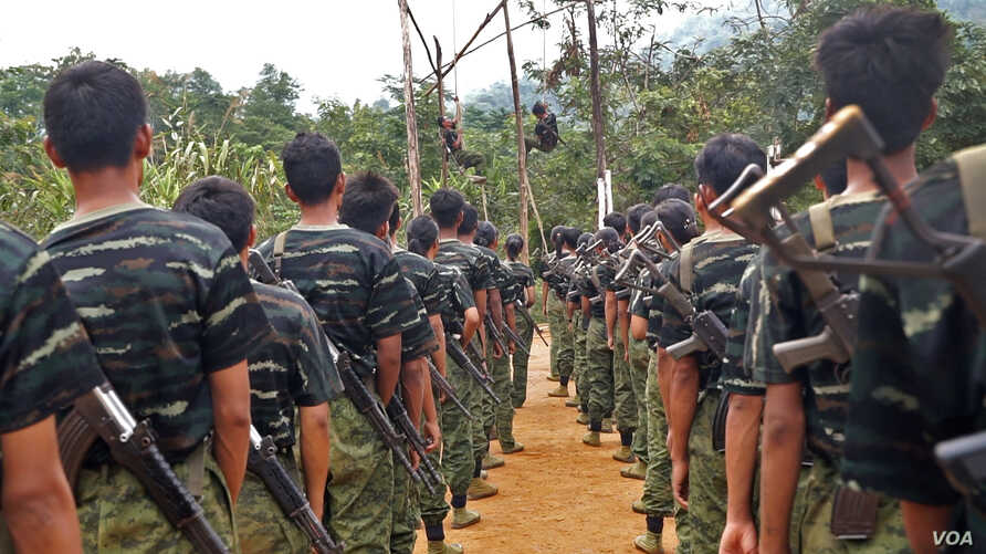 Arakan Army recruits scale the climbing ropes at the Laiza, Kachin State base camp.