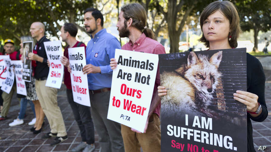 Emily Rohr, right, joins fur ban protesters with the People for the Ethical Treatment of Animals (PETA) prior to a news conference at Los Angeles City, Sept. 18, 2018.