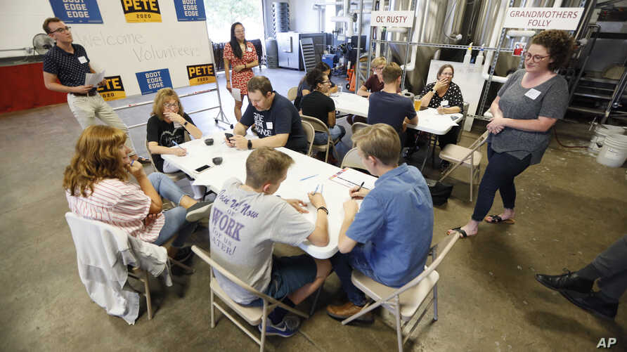 """Supporters for Democratic presidential candidate Pete Buttigieg meet at a local brewery for a """"relational phone bank"""", Aug. 29, 2019, in West Des Moines, Iowa."""