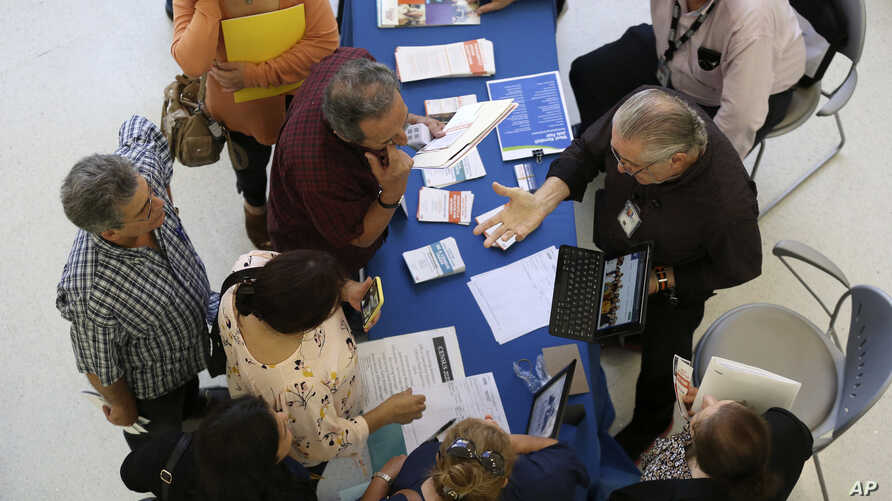 Alex Pereira, of the U.S. Census Bureau, right, talks with job applicants about temporary positions available with the 2020…