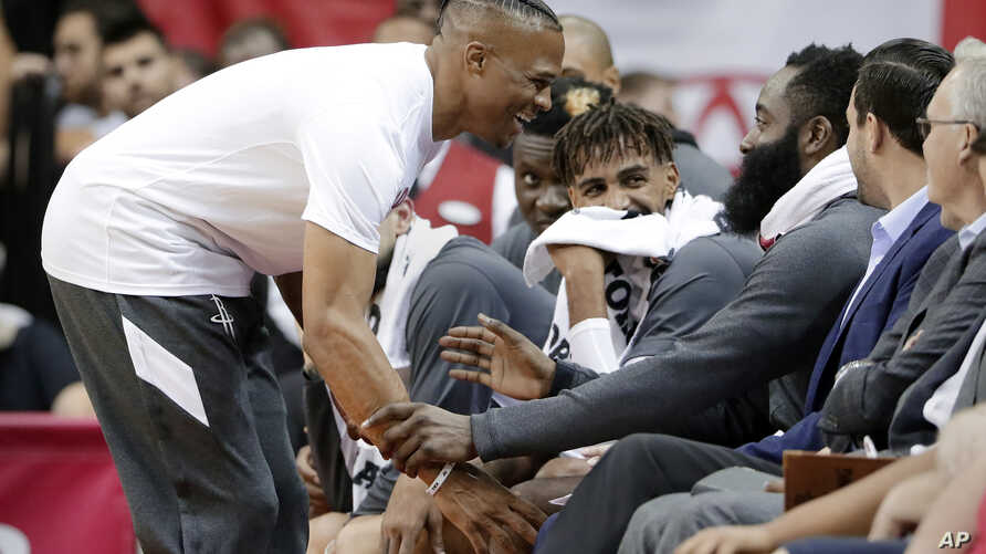 Houston Rockets guard Russell Westbrook, left, grabs at James Harden as they joke around at the bench during the second half of an NBA basketball preseason game against the Shanghai Sharks, Monday, Sept. 30, 2019, in Houston.