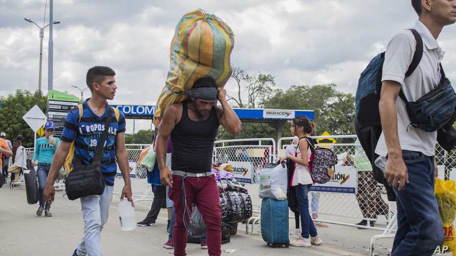 "A man carries a large load on his back, with the strap around his forehead, as he works as a ""lomo taxista,"" or taxi of the lower back, across the border from Cucuta, Colombia to Venezuela, Sept. 20, 2019."