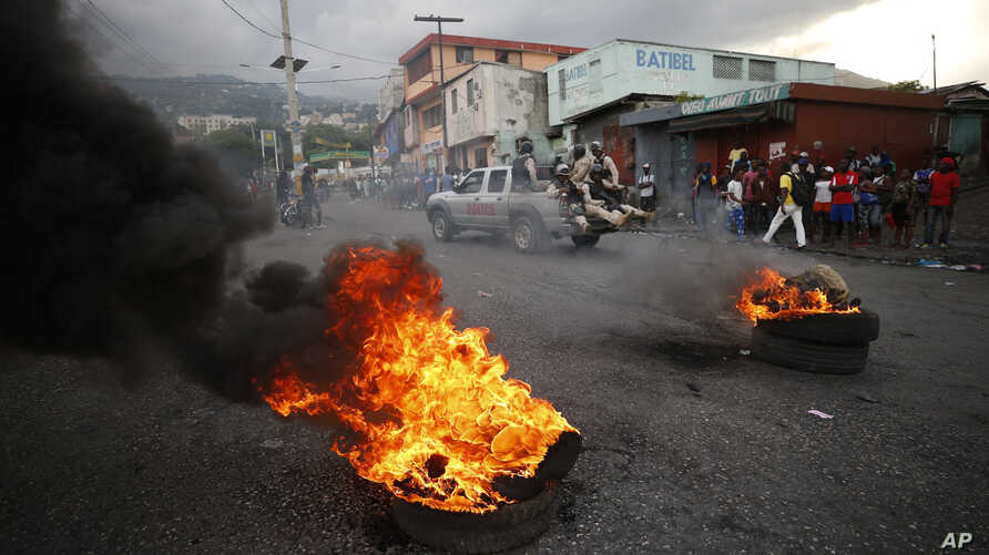 Police drive past burning tires lit by anti-government protestors, in Port-au-Prince, Haiti, Friday, Oct. 4, 2019. Thousands of…
