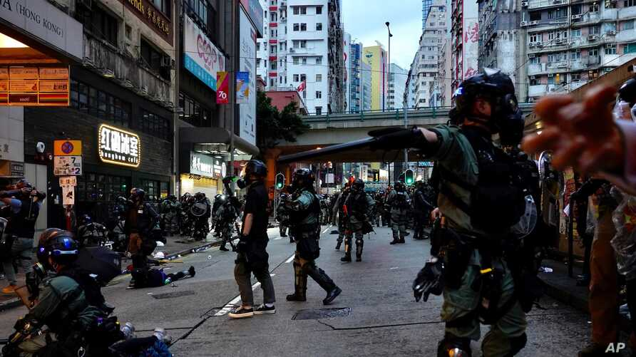 "Riot police tell journalists to leave while they arrest protesters in Hong Kong, Sunday, Oct. 6, 2019. Shouting ""Wearing mask…"