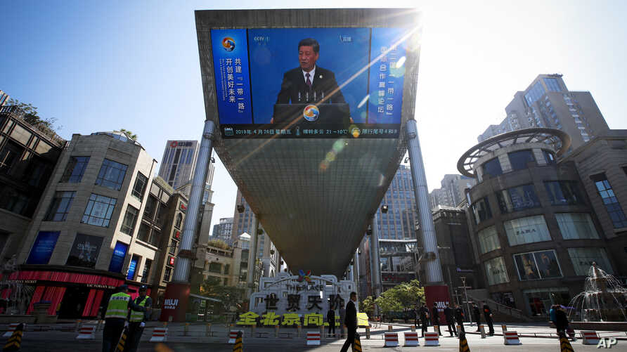 FILE - In this April 26, 2019, photo, traffic warden and securities stand guard near a TV screen broadcasting live of President