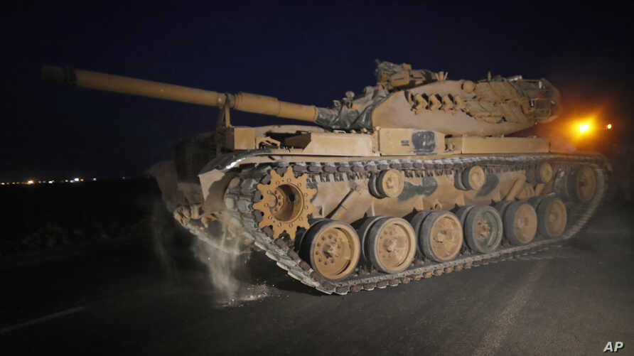 A Turkish army tank is driven to its new position, after was uploaded from a truck, on the Turkish side of the border between…