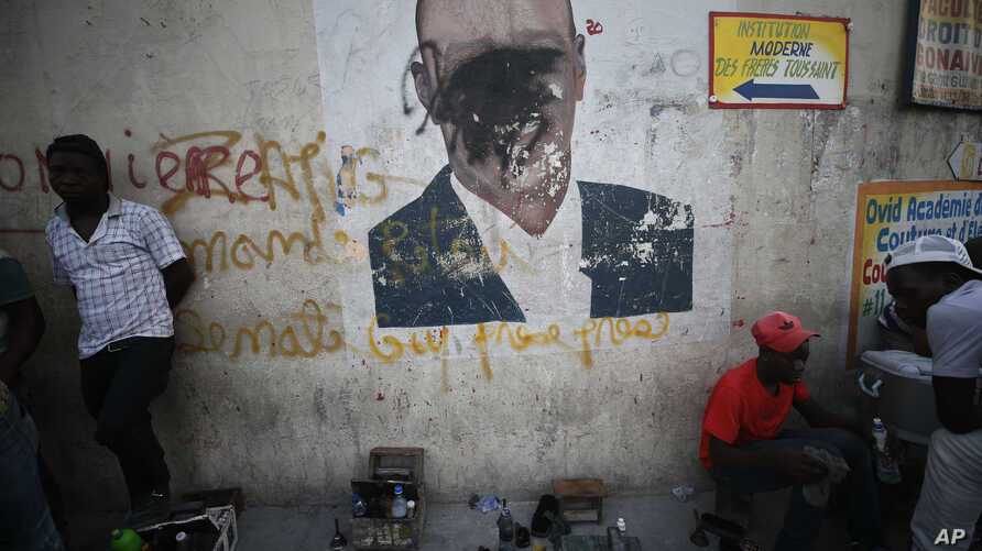 A man shines a client's shoes as another waits for business, in front of a wall painted with an image of President Jovenel…