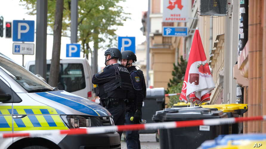 Police officers are seen at a crime scene in Halle, Germany, Wednesday, Oct. 9, 2019. A gunman fired several shots on Wednesday…
