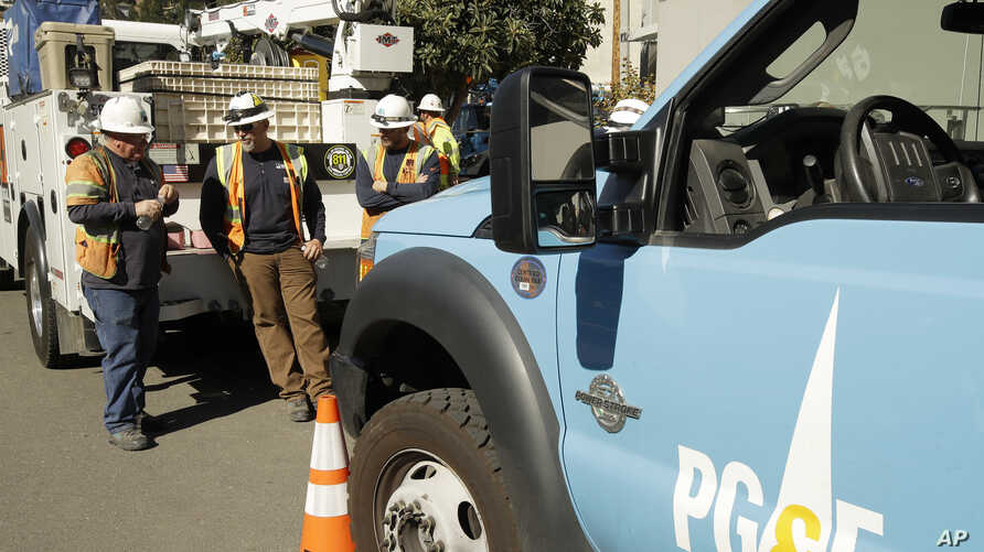 Pacific Gas & Electric and CalTrans workers stand near the Caldecott Tunnel Wednesday, Oct. 9, 2019, in Oakland, Calif. Pacific…