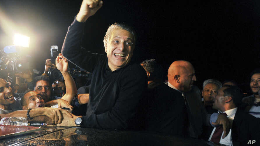 Tunisian presidential candidate and media mogul Nabil Karoui, waves as he is greeted by jubilant crowds after he was released from prison in Mannouba, Tunisia, Wednesday Oct. 9, 2019, just four days before the upcoming presidential runoff election.