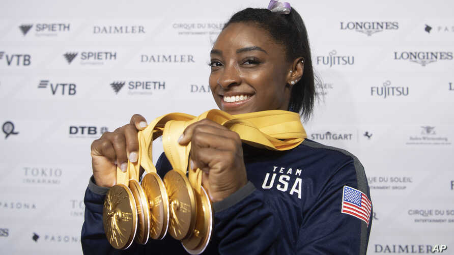 Simone Biles of the United States shows her five gold medals she won at the Gymnastics World Championships in Stuttgart, Germany, Oct. 13, 2019.