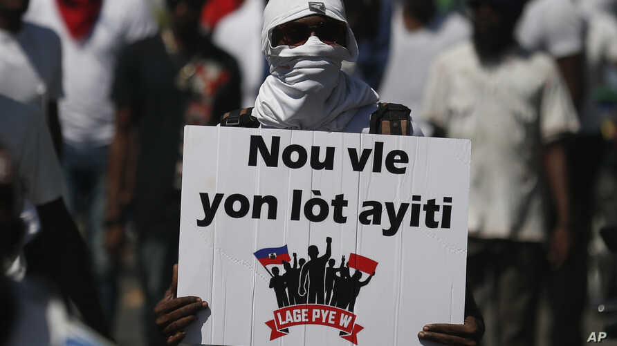 """A demonstrator carries the Creole message """"We want a different Haiti"""" during a march led by the art community to continue…"""