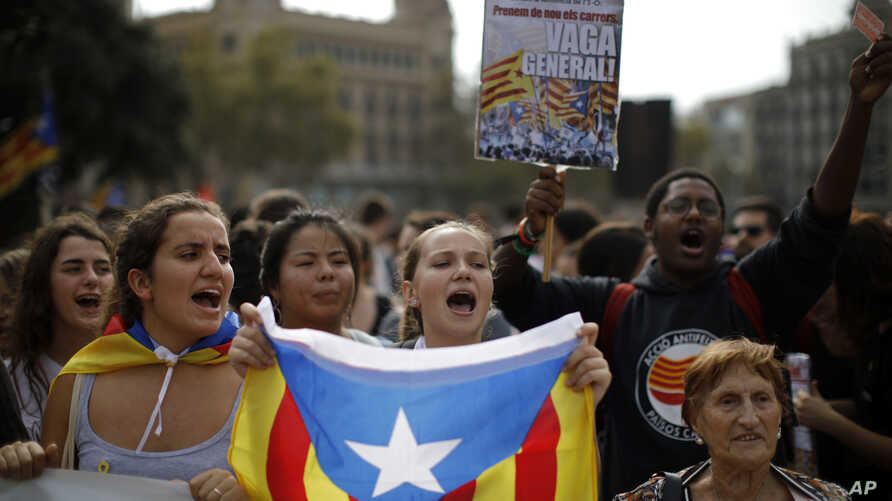 People wearing yellow ribbons in support of jailed pro-independence politicians and carrying Estelada pro-independence flags protest in Barcelona, Spain, Oct. 14, 2019.