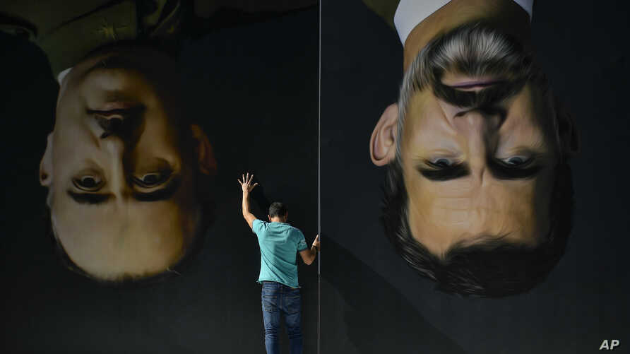 A man sets up upside down giant paintings of late Spanish dictator Francisco Franco, left, and Spanish King Felipe VI ahead of…