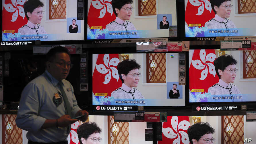 A shopper walks near televisions broadcasting live of Hong Kong Chief Executive Carrie Lam's speech in Hong Kong, on Wednesday,…