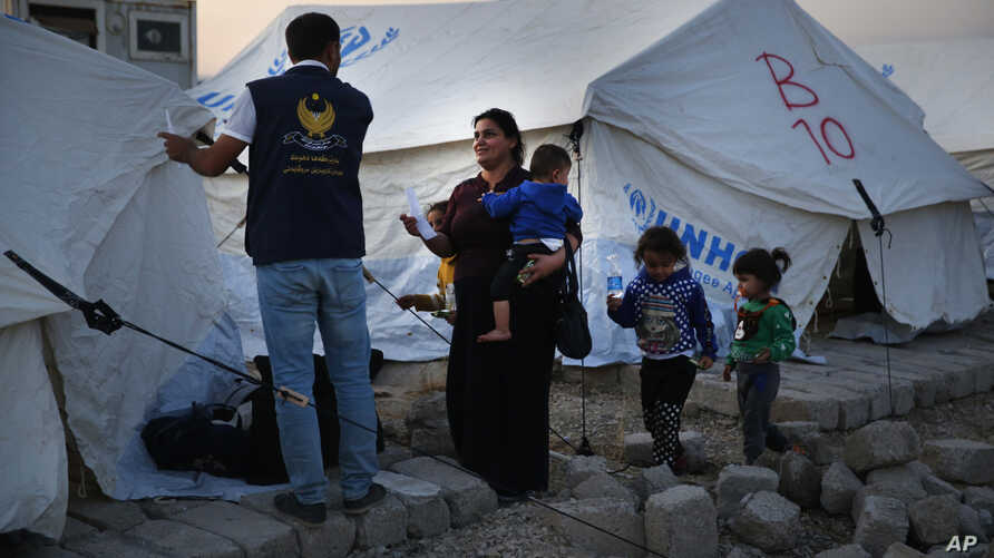 A Syrian woman with her children, who are newly displaced by the Turkish military operation in northeastern Syria, receives a tent from a Kurdish humanitarian worker upon her arrival at the Bardarash camp, north of Mosul, Iraq, Oct. 16, 2019.