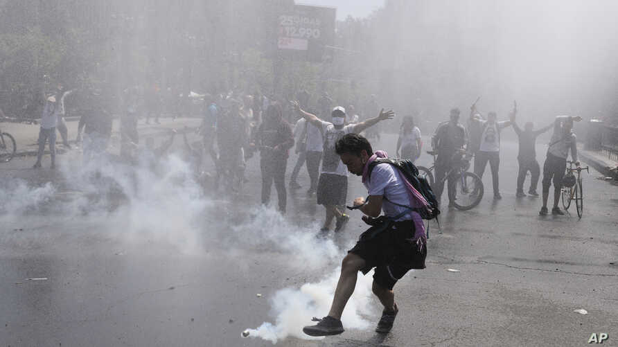 A protester kicks a tear gas canister during clashes with police in Santiago, Chile, Oct. 20, 2019.
