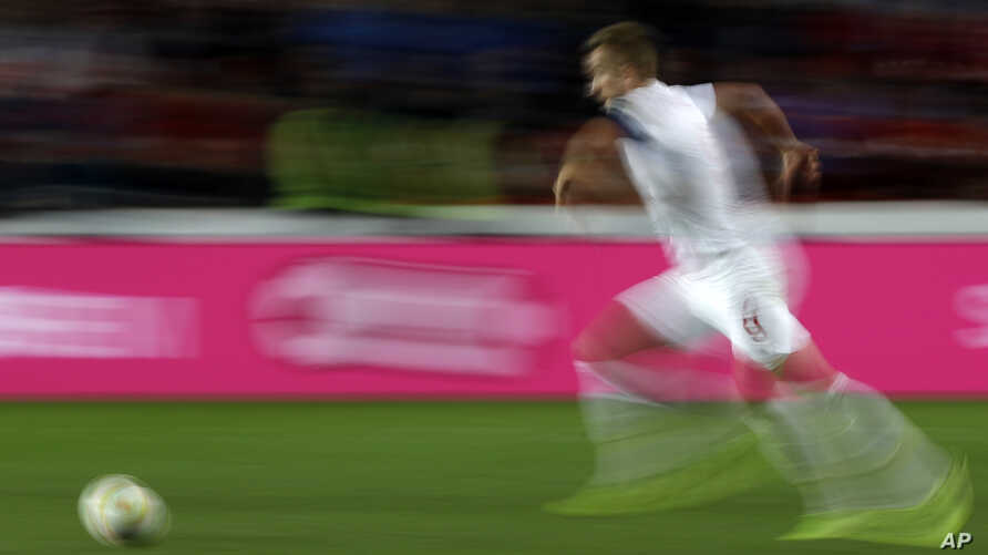 FILE - In this Oct. 11, 2019, file image taken with a slow shutter speed a soccer player runs for the ball during the Euro 2020 group A qualifying soccer match in Prague, Czech Republic.
