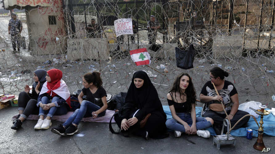 Anti-government protesters sit in front of a barbed-wire barrier on a road that leads to the Government House, during a protest in Beirut, Lebanon, Oct. 22, 2019.