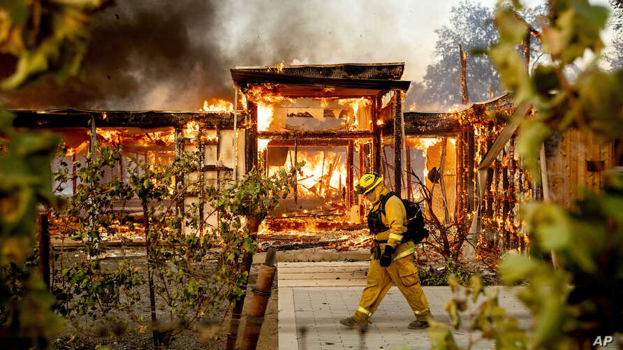 Woodbridge firefighter Joe Zurilgen passes a burning home as the Kincade Fire rages in Healdsburg, California, Oct 27, 2019.