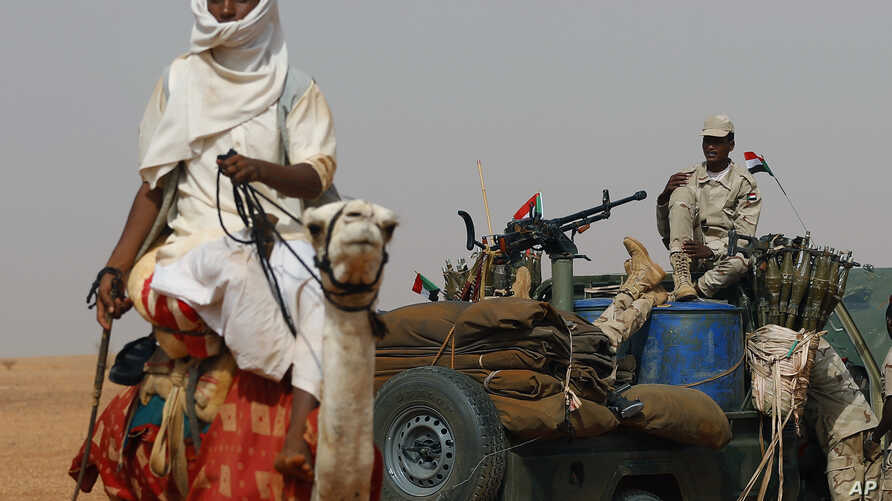 FILE - Gen. Mohammed Hamdan Dagalo, the deputy head of the military council sits on his vehicle surrounded by soldiers from the Rapid Support Forces, RSF, unit during a military-backed tribal rally, in the East Nile province, Sudan, June 22, 2019.