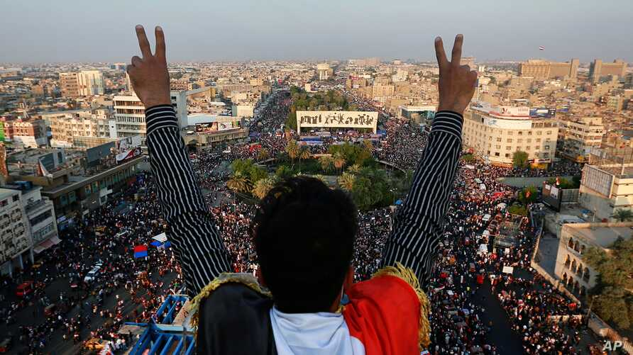A protester flashes the victory sign while anti-government protesters gather in Tahrir Square during ongoing protests in…