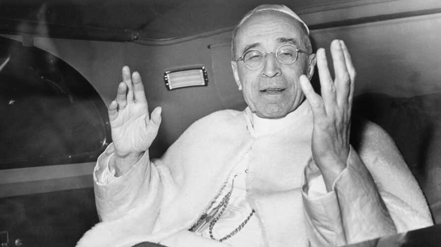 FILE - Pope Pius XII smiles as he waves with both arms, sitting in his car, in response to the cheers from a crowd gathered outside the papal summer residence, Nov. 29, 1955, just as the Pontiff leaves for the Vatican, about 18 miles away.