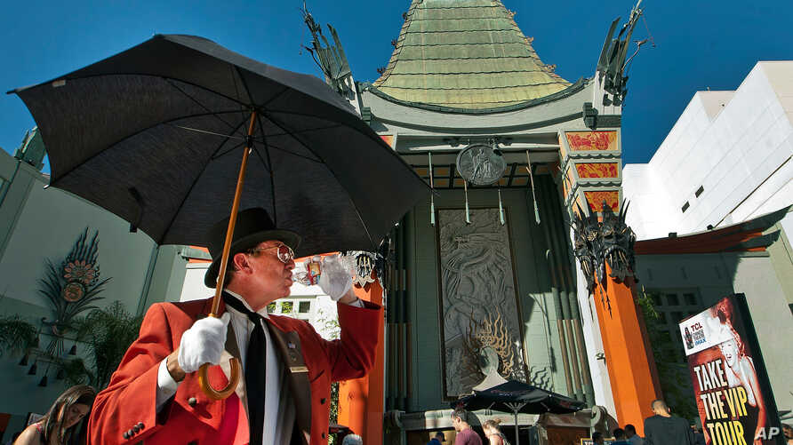 FILE - Gregg Donovan greets tourists in Hollywood outside the TCL Chinese Theatre in Los Angeles, Oct. 2, 2014. The theater, which opened in 1927, is one of the first stops for tourists visiting Los Angeles.