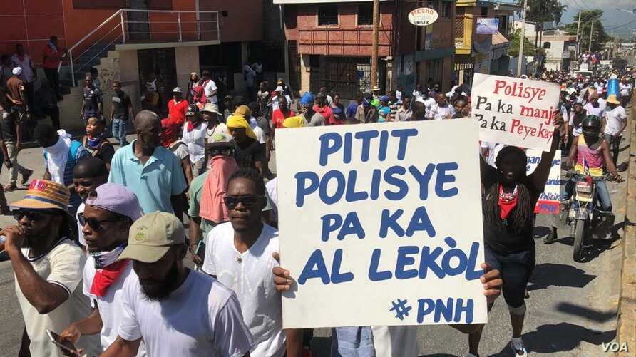 """Haiti police protester holds poster that reads: """"policemen's children can't go to school,"""" in Port au Prince, Haiti, Oct 27, 2019."""