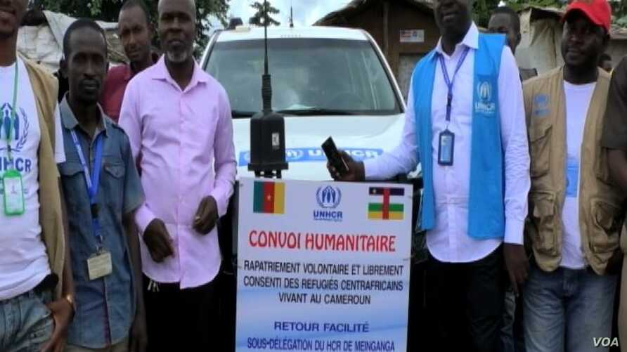 Humanitarian workers stand in front of convoy to transport CAR refugees back home, in Garoua Boulai, Cameroon, Oct. 23, 2019. (Moki Edwin Kindzeka/VOA)
