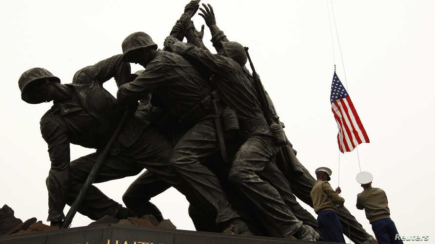 U.S. flags are briefly raised, saluted, then lowered by U.S. Marines during a ceremony honoring members of the military at the Iwo Jima Memorial (also called the U.S. Marine Corps War Memorial) in Arlington, Virginia, March 5, 2012.
