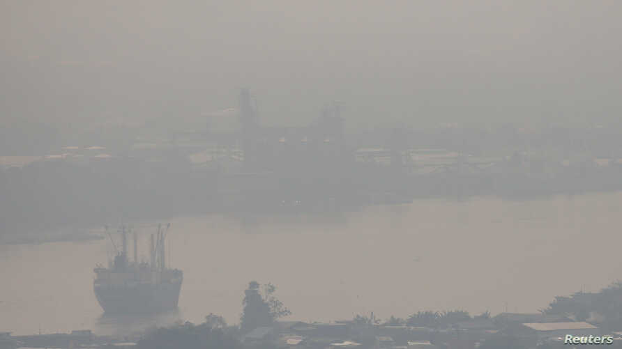 FILE - A cargo ship is seen through air pollution along the Chao Phraya river in Bangkok, Thailand, Jan. 11, 2019.